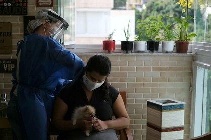 Imagen de archivo de la fisioterapeuta Ana Carolina Xavier de FamilyCare, un grupo que se especializa en cuidados fisioterapéuticos móviles y quien trabaja en la UCI del hospital de campo Lagoa-Barra con pacientes de COVID-19, siendo tratada por una colega con el método brasileño de fisioterapia llamado RTA (reequilibrio toracoabdominal), luego de que fue diagnosticada con COVID-19, en su casa en Río de Janeiro, Brasil. 25 de junio, 2020. REUTERS/Ricardo Moraes