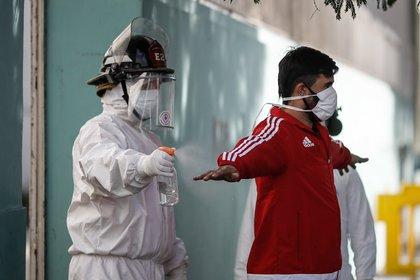 Un bombero rocía con alcohol a un hombre durante una jornada de tomas de pruebas de coronavirus este martes, en el barrio Constitución de Buenos Aires, Argentina (EFE/ Juan Ignacio Roncoroni)