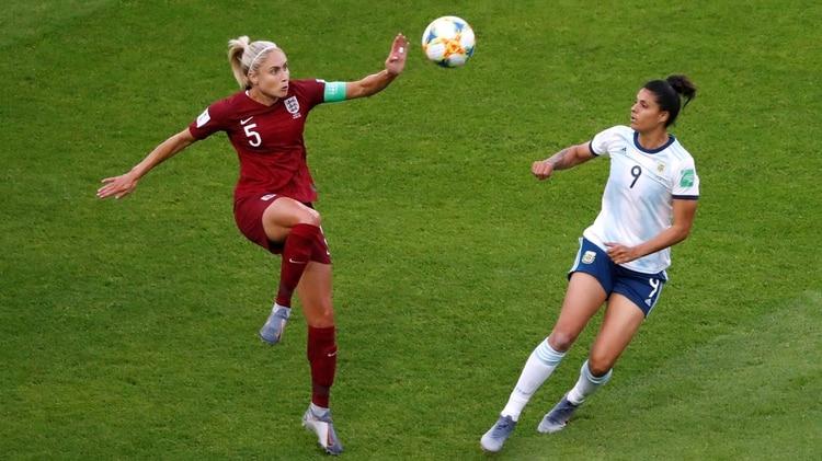 Steph Houghton, de Inglaterra, le gana en el duelo por el balón a Sole Jaimes (REUTERS/Bernadett Szabo)
