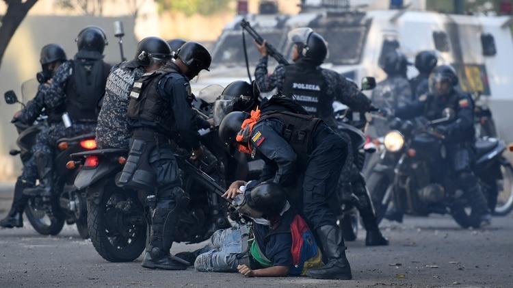 La Guardia Nacional Bolivariana reprimiendo a manifestantes en una marcha en Venezuela (Photo by Federico PARRA / AFP)