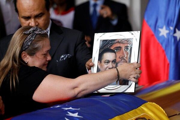 Luz Albán pone una foto sobre el ataúd de su hermano Fernando Albán durante una ceremonia en la Asamblea Nacional de Caracas (REUTERS/Marco Bello)