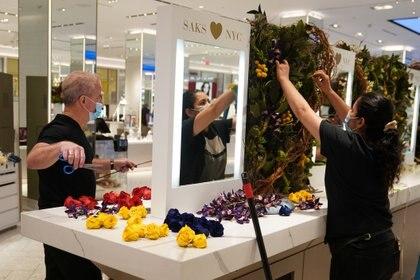 Trabajadores colocan una exhibición de flores en Saks 5th Avenue en el distrito de Manhattan de la ciudad de Nueva York, el 24 de junio de 2020 (REUTERS/Carlo Allegri)
