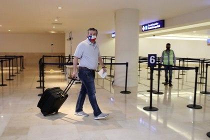 Le sénateur Ted Cruz (républicain du Texas) porte ses bagages à l'aéroport international de Cancun, au Mexique, le 18 février 2021, avant de monter à bord de son avion pour les États-Unis.  (Reuters)