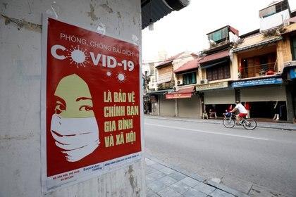 Un póster advierte sobre el COVID-19 en una calle de Hanoi