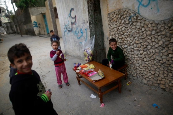 A Palestinian child sells sweets outside a house in the al-Shati refugee camp in Gaza City on January 4, 2018. / AFP PHOTO / MOHAMMED ABED