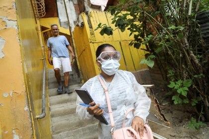 Un médico con máscara protectora camina después de una entrevista en el barrio de bajos ingresos de Las Mayas, mientras aumentan los casos en medio del brote de la enfermedad del coronavirus (COVID-19), en Caracas.