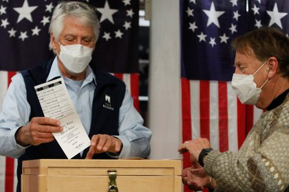 Selectman Les Otten drops a ballot in a box shortly after midnight for the U.S. presidential election at the Hale House at Balsams Hotel in the hamlet of Dixville Notch, New Hampshire, U.S., November 3, 2020. REUTERS/Ashley L. Conti