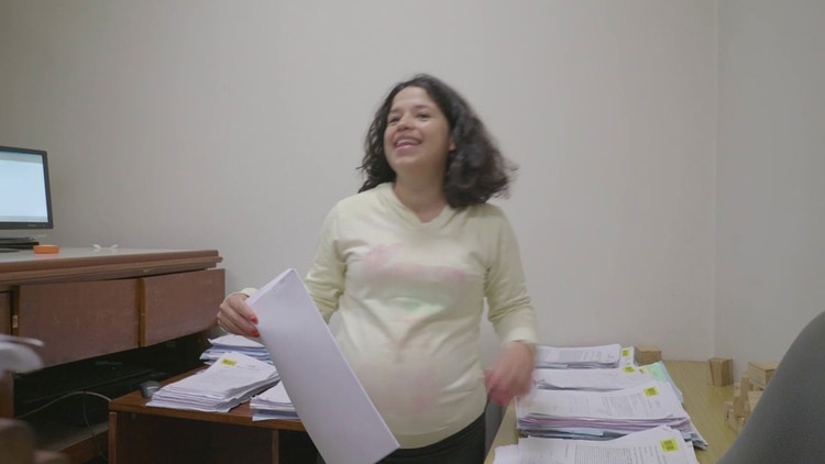 En pleno trabajo. Johana trabaja como empleada adminstrativa del Poder Judicial. En la foto estaba esperando a Augusto. (Captura video Bolsa de Comercio de Córdoba).