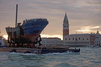La llegada de la obra del islandés Christoph Bucher, 'Barca Nostra', el barco de pesca con 700 inmigrantes a bordo, que se hundió en el Mar Mediterráneo en 2015. (EFE)
