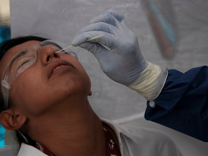 A patient gestures as a health worker in personal protective equipment (PPE) conducts a test for the coronavirus disease (COVID-19), in the municipality of Tlahuac, one of the highly contagious zones of the city, as the coronavirus disease (COVID-19) outbreak continues in Mexico City, Mexico July 15, 2020. REUTERS/Carlos Jasso