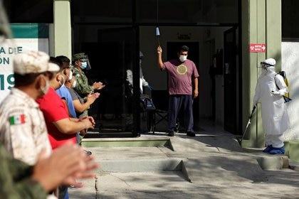 Militares y trabajadores de la salud aplauden al paciente Arturo Cardoso, quien se recuperó de la enfermedad del coronavirus (COVID-19), al ser dado de alta de un hospital militar en Ciudad Juárez, México, el 7 de octubre de 2020 (Reuters/ José Luis González)