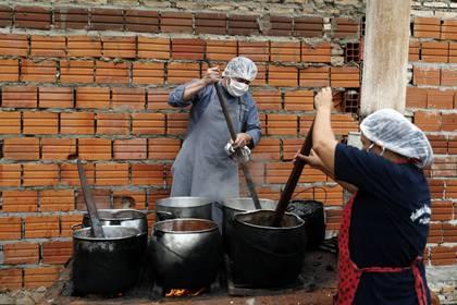 """Walter Ferreira, a la izquierda, y Laura Dure preparan estofado en un comedor social que alimenta a unas 300 personas cada día en Luque, Paraguay, el lunes 11 de mayo de 2020. En toda la región, se espera que casi 30 millones de personas más se vean en """"situaciones de pobreza"""" y otros 16 millones en pobreza extrema, según las estimaciones de Naciones Unidas. (AP Foto/Jorge Sáenz)"""