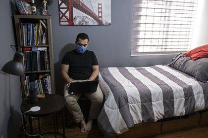 El médico mexicano Alex González usa su computadora portátil después de su turno.