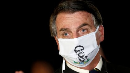 FILE PHOTO: Brazil's President Jair Bolsonaro speaks with journalists while wearing a protective face mask as he arrives at Alvorada Palace, amid the coronavirus disease (COVID-19) outbreak, in Brasilia, Brazil, May 22, 2020. REUTERS/Adriano Machado/File Photo