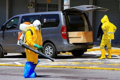 Trabajadores de una funeraria con trajes especiales, como medida de protecci�n contra la covid-19, se llevan el cuerpo de una persona, que aparentemente muri� por s�ntomas relacionados con el coronavirus, en un ata�d de madera en Quito (Ecuador). EFE/Jos� J�come/Archivo