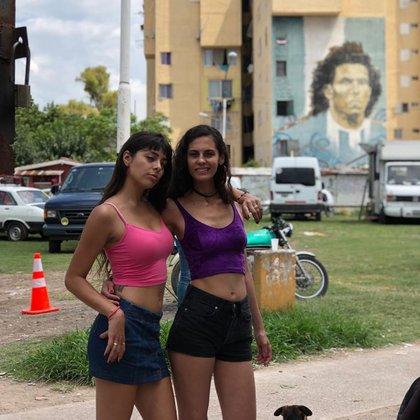 Tamara junto a Yésica Glikman. De fondo: el muro de Carlos Tevez que pintaron los vecinos de Fuerte Apache en homenaje al futbolista