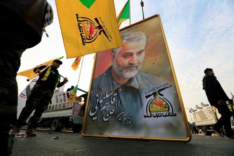 La milicia iraquí Kataib Hezbollah sostiene la foto del General de División iraní Qassem Soleimani, mientras se reúnen antes del funeral del comandante de la milicia iraquí Abu Mahdi al-Muhandis, que murió en un ataque aéreo en el aeropuerto de Bagdad, Irak, el 4 de enero de 2020 (REUTERS/Thaier al-Sudani)