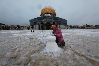 Una niña juega junto a la Cúpula de la Roca en el complejo conocido por los judíos como el Monte del Templo y por los musulmanes como el Noble Santuario durante una mañana nevada en la Ciudad Vieja de Jerusalén, el 18 de febrero de 2021. REUTERS / Ammar Awad