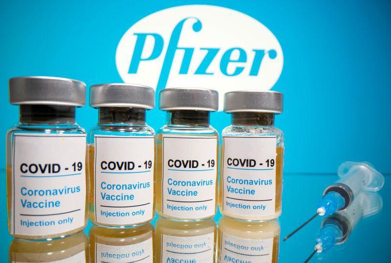 Una jeringa médica frente a frascos con el logotipo de Pfizer (Foto: Reuters)