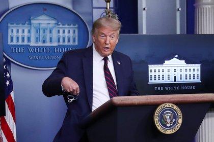 Trump saca su mascarilla de su bolsillo en la conferencia de prensa. Foto: REUTERS/Leah Millis