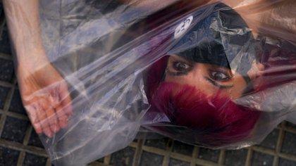 Una de las imágenes más fuertes de la manifestación: una intervención impactante para generar conciencia: 12 mujeres enfundadas en bolsas de plástico, desnudas, y enfrentando a la sociedad con el espejo de un asesinato (Foto: Franco Fafasuli)