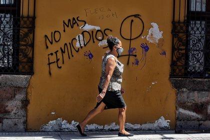 Una mujer camina frente a un mural que reclama que no haya más femicidios (EFE/Gustavo Amador)
