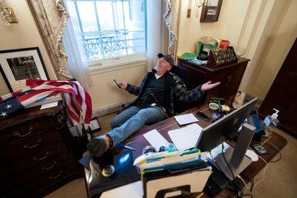 Un seguidor de Donald Trump se sentó en el escritorio de la presidenta de la Cámara de Representantes de Estados Unidos, Nancy Pelosi, luego de irrumpir de manera violenta en el Capitolio en Washington DC (EFE)