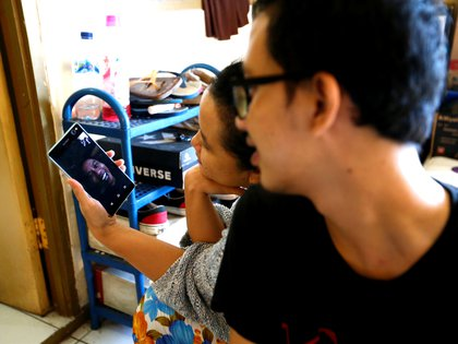 People make a video call with their family after prayers for Eid al-Fitr, the Muslim festival marking the end the holy fasting month of Ramadan, at a boarding house in Jakarta, Indonesia, amid the coronavirus disease (COVID-19) outbreak, May 24, 2020. REUTERS/Ajeng Dinar Ulfiana
