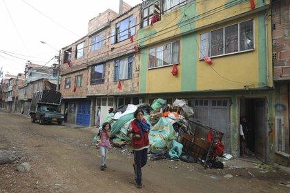 Vecinos que necesitan comida colocaron trozos de tela roja en sus ventanas para alertar a empleados del Ayuntamiento, que reparten bolsas de alimentos gratis para los necesitados durante una cuarentena para combatir la expansión del coronavirus, en Bogotá, Colombia, el miércoles 27 de mayo de 2020. (AP Foto/Fernando Vergara)