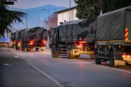 Camiones militares italianos atraviesan las calles de Bérgamo después de que el ejército se desplegó para trasladar ataúdes de los cementerios de la ciudad, que estuvo en el centro del brote de la enfermedad del coronavirus. Fotografía tomada el 18 de marzo de 2020. (Sergio Agazzi via REUTERS)