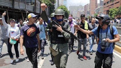 Un miembro de la Guardia Nacional Bolivariana se une a los manifestantes de la oposición durante las protestas en Caracas. (Reuters)
