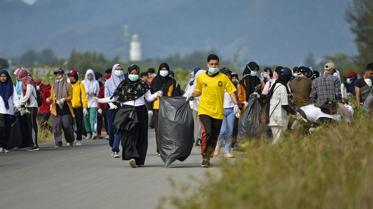 Voluntarios limpiando basura de las playas (AFP)