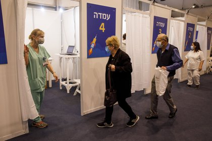 An elderly couple enter a cubicle inside a Covid-19 mass vaccination center at Rabin Square in Tel Aviv, Israel, on Monday, Jan. 4, 2020. Israel plans to vaccinate 70% to 80% of its population by April or May, Health Minister Yuli Edelstein said on Monday, pressing ahead with a program that promises an earlier-than-forecast economic recovery.