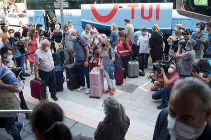 Turistas llegan a su hotel en Palma de Mallorca, España, este lunes.