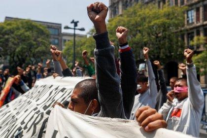 Estudiantes de Azotinapa  levantan los puños durante una protesta frente a la Corte Suprema de Justicia, antes del sexto aniversario de la desaparición de 43 estudiantes de la Escuela de Formación de Maestros de Ayotzinapa, en la Ciudad de México, México 23 de septiembre de 2020.