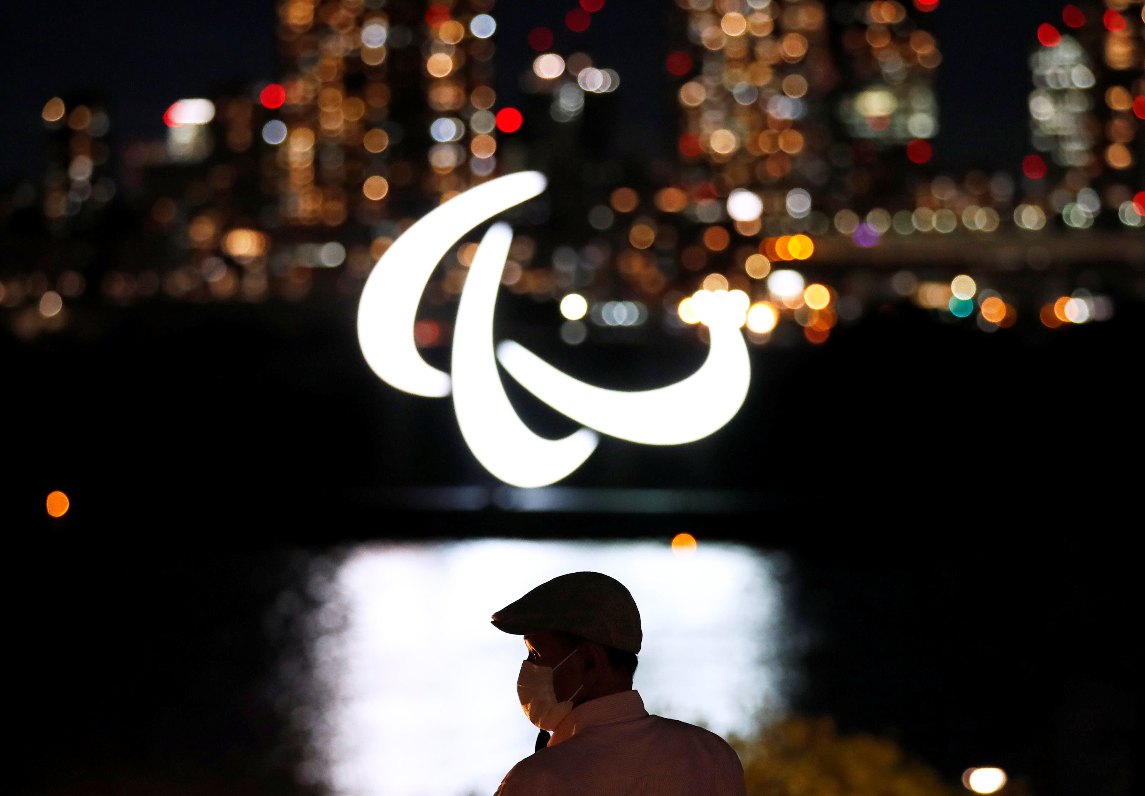 A visitor wearing a protective mask looks at an illuminated Paralympic symbol at the waterfront area of Odaiba Marine Park, ahead of the opening ceremony of the 2020 Tokyo Paralympic Games that have been postponed to 2021 due to the COVID-19 pandemic, in Tokyo, Japan August 20, 2021  REUTERS/Issei Kato