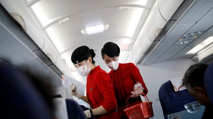 FILE PHOTO: Flight attendants wearing face masks and gloves following the coronavirus disease (COVID-19) outbreak are seen inside a Sichuan Airlines aircraft before the flight takes off from Xichang Qingshan Airport in Xichang, Sichuan province, China June 16, 2020.  REUTERS/Carlos Garcia Rawlins/File Photo