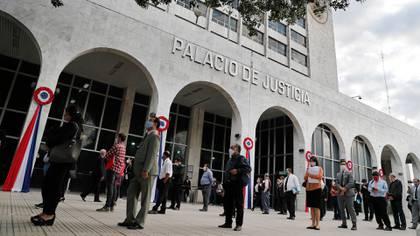 Personas hacen fila para ingresar al Palacio de Justicia de Asunción manteniendo la distancia social. Al ingresar, deben lavarse las manos y se les toma la temperatura.