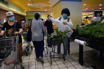 Personas usan mascarillas mientras compran verduras en un supermercado, después de los nuevos casos de infecciones de la enfermedad coronavirus (COVID-19) en Beijing, China, el 15 de junio de 2020 (Reuters/ Tingshu Wang)