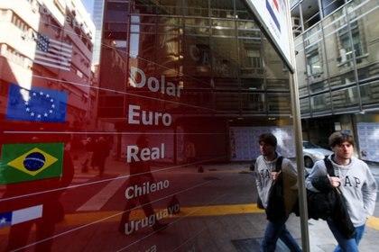 Foto de archivo. Un hombre pasa junto a un tablero electrónico que muestra los tipos de cambio de divisas, en Buenos Aires, Argentina, 20 de agosto de 2019. REUTERS / Agustin Marcarian