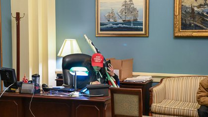 Un partidario de Trump se sienta en un escritorio después de invadir el edificio del Capitolio  (Foto de Saul LOEB / AFP)