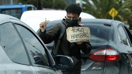 Un hombre vende dulces y pide ayuda en un semáforo, en Bogotá; (Colombia). EFE/ Mauricio Duenas Castañeda/Archivo