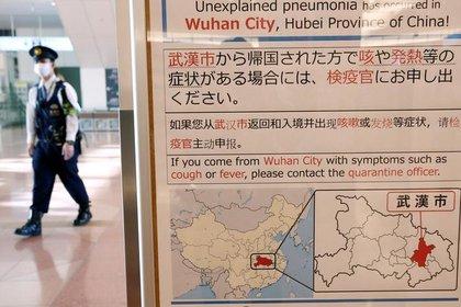 Foto de archivo de un policía con una mascarilla pasando cerca de un cartel que informa sobre el brote de coronavirus en Wuhan, China, en el aeropuerto de Haneda en Tokio (20 de 2020, Reuters/ Kim Kyung-Hoon)