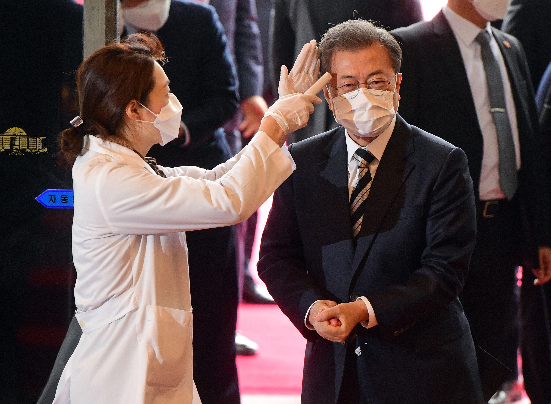 El presidente Moon Jae-in se somete a una prueba de temperatura a su llegada a la Asamblea Nacional en Seúl, Corea del Sur, el 28 de febrero de 2020 (Yonhap, a través de los editores de REUTERS)