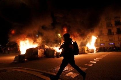 Una barricada con contenedores de basura fue prendida fuego en una calle de Barcelona durante la cuarta noche de manifestaciones para pedir la liberación de Pablo Hásel (REUTERS/Albert Gea)