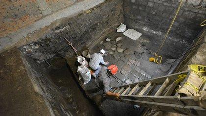 Proceso de excavación y limpieza de un piso de lajas del periodo Virreinal Temprano (Foto: INAH)