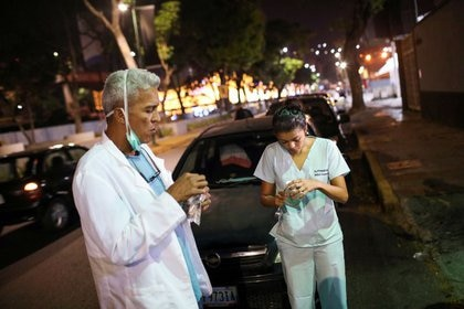 Los doctores Carlos Martínez y María Martínez comen un refrigerio mientras esperan en la fila para obtener combustible en una gasolinera, durante una cuarentena a debido al brote de la enfermedad por coronavirus (COVID-19), en Caracas. 7 de abril 2020. REUTERS/Manaure Quintero