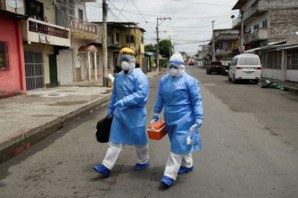 Médicos que forman parte de una unidad de rápida respuesta del Ministerio de Salud ecuatoriano caminan a una residencia para tomar muestras de personas que se sospecha tienen COVID-19, en Guayaquil, (Reuters)