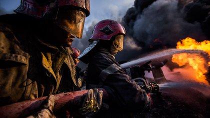 En equipos de cinco, los bomberos luchan para intentar sofocar las llamas. El intenso calor y los gases desprendidos hace que los bomberos sólo puedan estar unos minutos en primera línea (Pablo Cobos)