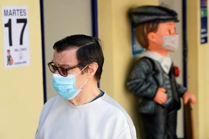 """Un hombre junto a una estatua con la vestimenta tradicional de """"Chulapo"""", ambos con mascarilla, en Madrid (Reuters)"""